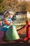 Petite fille jouant à la cour de jeu Photographie stock libre de droits