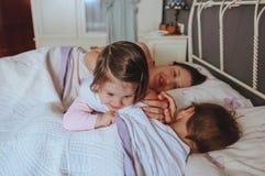 Petite fille jouant au-dessus du garçon se situant dans le lit image libre de droits