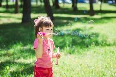 Petite fille jouant avec des bulles de savon Image stock