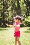 Petite fille jouant avec des bulles de savon Photos stock