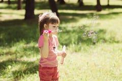 Petite fille jouant avec des bulles de savon photo libre de droits