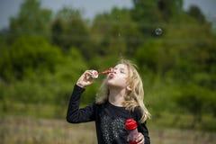 Petite fille jouant avec des bulles de savon Photographie stock libre de droits