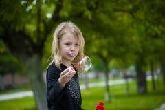 Petite fille jouant avec des bulles de savon Images stock