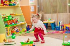 Petite fille jouant avec des jouets dans la salle de jeux Photographie stock