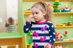Petite fille jouant avec des jouets dans la salle de jeux Image libre de droits