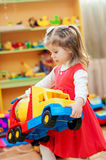 Petite fille jouant avec des jouets dans la salle de jeux Photographie stock libre de droits