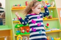 Petite fille jouant avec des jouets dans la salle de jeux Images libres de droits
