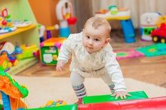 Petite fille jouant avec des jouets dans la salle de jeux Images stock