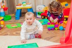Petite fille jouant avec des jouets dans la salle de jeux Image stock