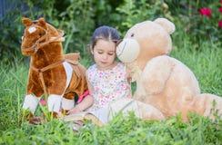 Petite fille jouant avec des jouets sur l'herbe verte dehors dans l'arrière-cour Image stock