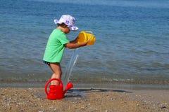 Petite fille jouant avec des jouets sur la plage Image libre de droits
