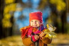 Petite fille jouant avec des lames d'automne Photo stock