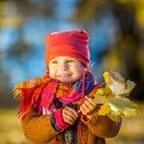 Petite fille jouant avec des lames d'automne photos stock