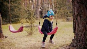 Petite fille jouant avec des oscillations dans la forêt banque de vidéos