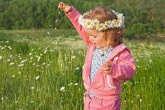Petite fille jouant avec des pétales de fleur photos stock