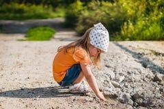 Petite fille jouant avec des pierres Photos stock