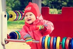 Petite fille jouant avec l'abaque sur le terrain de jeu Image libre de droits