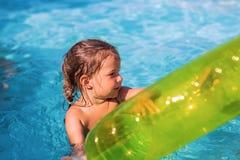Petite fille jouant avec l'anneau gonflable dans le poo extérieur de natation photos stock