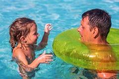 Petite fille jouant avec l'anneau gonflable et son papa dans extérieur photographie stock libre de droits