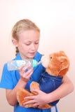Petite fille jouant avec l'ours de nounours Images stock