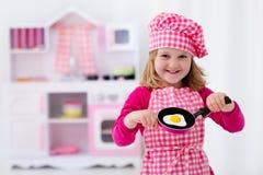 Petite fille jouant avec la cuisine de jouet photographie stock libre de droits