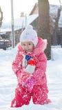 Petite fille jouant avec la neige Photographie stock