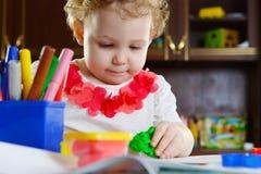 Petite fille jouant avec la pâte d'argile Image libre de droits
