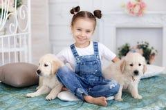 Petite fille jouant avec le chien d'arrêt de chiots Image libre de droits