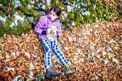 Petite fille jouant avec le chiot dans la forêt Photographie stock