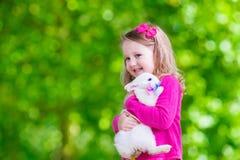 Petite fille jouant avec le lapin Photo stock
