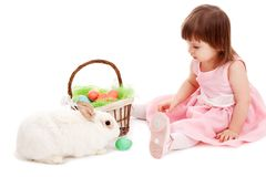 Petite fille jouant avec le lapin d'eatser de fourrure Image libre de droits