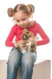 Petite fille jouant avec le lapin de Pâques sur un fond blanc Photographie stock