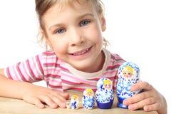 Petite fille jouant avec le matryoshka et le sourire Photos stock
