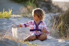 Petite fille jouant avec le sable photos stock