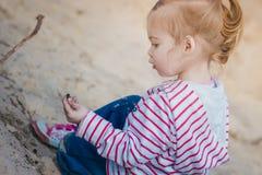 Petite fille jouant avec le sable dans la forêt Images stock