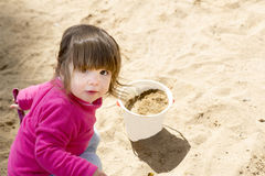 Petite fille jouant avec le sable et le seau dans le bac à sable Photographie stock libre de droits