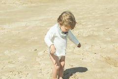 Petite fille jouant avec le sable sur la plage photos stock