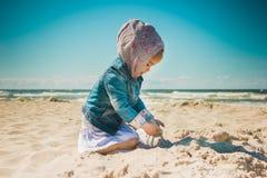 Petite fille jouant avec le sable sur la plage Photographie stock