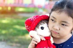 Petite fille jouant avec son bébé - poupée Image stock