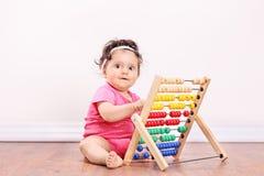 Petite fille jouant avec un abaque posé sur le plancher Photographie stock libre de droits