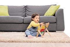 Petite fille jouant avec un abaque posé sur le plancher Image libre de droits
