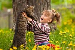Petite fille jouant avec un chat photos stock