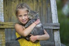 Petite fille jouant avec un chat nature images stock