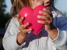 Petite fille jouant avec un coeur en plastique rouge elle le tient dans des ses mains Images stock