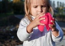 Petite fille jouant avec un coeur en plastique rouge elle le tient dans des ses mains Image stock