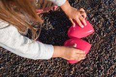 Petite fille jouant avec un coeur en plastique rouge elle le tient dans des ses mains Photo stock