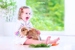 Petite fille jouant avec un lapin Photographie stock libre de droits