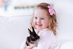 Petite fille jouant avec un vrai lapin d'animal familier Image libre de droits