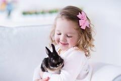 Petite fille jouant avec un vrai lapin d'animal familier Photo stock