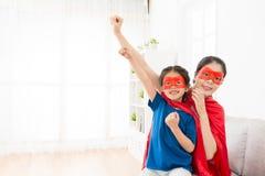 Petite fille jouant comme super héros avec la jeune mère Image libre de droits